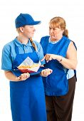 Teenage fast food worker getting instructions from her middle-aged boss.  Isolated on white.