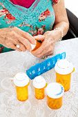 Senior woman sorting her pills for the week.