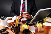 Closeup view of a very cluttered businessmans desk. Man is holding a coffee cup and crumpled papers