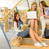 Three teenage female studying together on high school library stairs