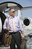 Senior glücklich kaufmann mit dem Flugzeug mit Gepäck auf dem Flugplatz stehen