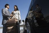 Low angle view of business couple standing together by car at airfield