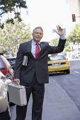 Senior businessman hailing a taxi cab in city