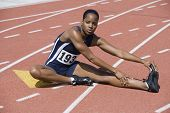 Full length of African American woman in sportswear stretching on race track