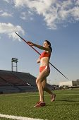 Female athlete in sportswear throwing javelin