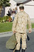 Rear view of soldier returning home with family waiting in background
