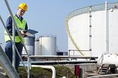 Engineer with a clipboard taking notes of the quality and state of oil silos of a petrochemical indu