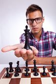 young man chess player with eyeglasses holding up his king, on gray background