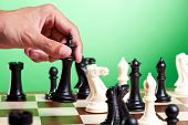Human hand moves king on chessboard. Green background