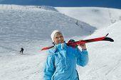 Esquí de explotación femenina esquiador; chaqueta azul; orientación horizontal