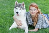 young happy woman with haski dog on green grass