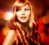 Beautiful Girl With Shiny Red Long Hair over Blinking Holiday Background.Surprised Woman