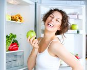 Healthy Eating Concept .Diet. Beautiful Young Woman near the Refrigerator with healthy food. Fruits
