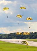 Silhouettes of the army skydiver team against dramatic sky over a drop zone on a battlefield.