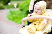 Smiling baby girl sitting in a stroller