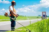 stock photo of trimmers  - Road landscaper cutting grass along the road using string lawn trimmer - JPG