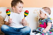 foto of maracas  - Cute little sister and her brother sitting with maracas on sofa - JPG