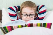 stock photo of spectacles  - Little cute boy in glasses reading book in bed - JPG