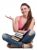 Beautiful student girl sitting with books on a white background, holding out her hand.