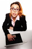 Fun overhead portrait of a young businesswoman sitting at her laptop computer wearing glasses and looking up expectantly at the camera