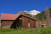 Old wooden buildings in the Crystal Mill Ghost Town on a bright sunny day with a snow capped mountai