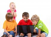 happy surprised children playing and learning with laptop, over white