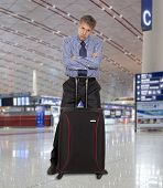 Flight delay. Sad businessman with a suitcase at the airport