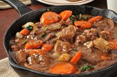 stock photo of stew  - A skillet of beef stew with carrots pearl onions and mushrooms in a burgundy wine sauce - JPG