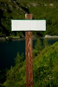 Poste indicador en blanco, vacío, en un paisaje de montaña