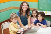 Portrait of beautiful teacher and students with laptop in classroom