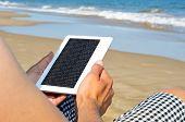 a man reading on an e-book on the beach