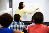 pic of 11 year old  - Teacher Standing In Class Using Interactive Whiteboard - JPG