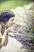 stock photo of clary  - Vintage photo of young woman smelling sage - JPG