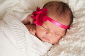 stock photo of sleeping  - Headshot of a sleeping 8 day old newborn baby girl wearing a pink flower headband - JPG