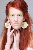 Beautiful Redhaired Girl With Lemon Slices In Ears