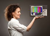 woman holding a television with her hand