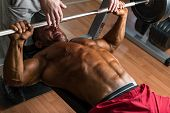 stock photo of muscle builder  - shirtless body builder doing bench press for chest - JPG