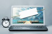 laptop with blank note on blue background