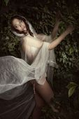 beautiful fantasy woman with white veil in forest