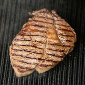 Rib-eye steak being cooked on griddle plate