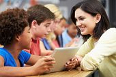 stock photo of 6 year old  - Pupils In Class Using Digital Tablet With Teacher - JPG