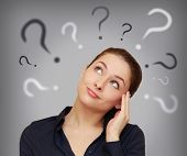 stock photo of cheer-up  - Beautiful business woman with question mark above the head looking up on grey background - JPG