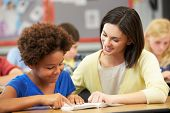 picture of 11 year old  - Teacher Reading With Female Pupil In Class - JPG