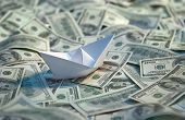 Origami paper boat at sea of money