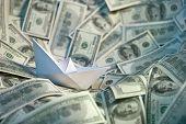 Paper ship at sea of money
