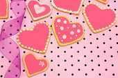 stock photo of poka dot  - Hand decorated heart shaped cookies with ribbon on pink patterned background - JPG