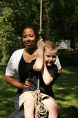 picture of babysitter  - a babysitter pushing a child on a tire swing - JPG