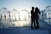Silhouette Of Young Couple Near Ice Wall With Sculptures At Winter Day.