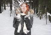 Girl In Hood With Fur Throws Up Snow In The Woods At Winter.