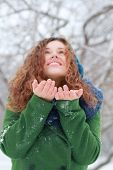 Pretty Girl Catches Snow By Palms And Looks Up At Winter Day In Park. Focus On Hands